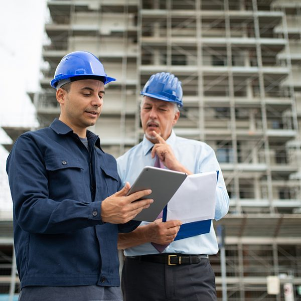 Architect and site manager using a construction ERP software installed in a tablet